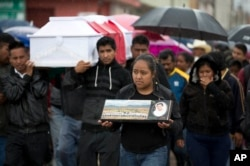 FILE - A young woman walks with a photo of Jesus Cadena in his funeral procession in Nochixtlan, Oaxaca state, Mexico, June 21, 2016. It was two days after he was killed in a clash between police and striking teachers.