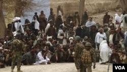 Pasukan nasional Afghanistan mengawasi ratusan warga Afghanistan yang berkumpul di luar pangkalan militer AS di distrik Panjwai, Kandahar pasca insiden penembakan (11/3).