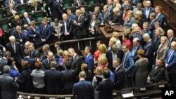Opposition lawmakers block the podium, as Parliament Speaker Marek Kuchcinski opens the parliament session, only to declare a break till Thursday, in Warsaw, Poland, Jan. 11, 2017.