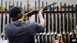 """Seorang pria AS memeriksa senjata api jenis """"shotgun"""" di sebuah toko senjata api di College Station, Texas. (Foto: ilustrasi)"""