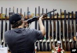 Seorang pelanggan mencoba senjata di sebuah toko senjata api di AS (foto: dok).