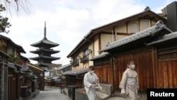 Dua perempuan berjalan di tengah keadaan darurat akibat wabah Covid-19 di Kyoto, Jepang 13 Januari 2021. (Foto: Kyodo via REUTERS)