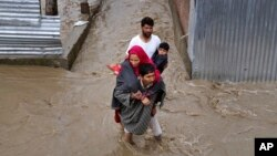 Kashmiri men assist a woman and a child to evacuate from a flooded area in Srinagar, Indian-controlled Kashmir, Monday, March 30, 2015.