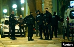 French special police forces secure the area as shots are exchanged in Saint-Denis, France, near Paris, Nov. 18, 2015.