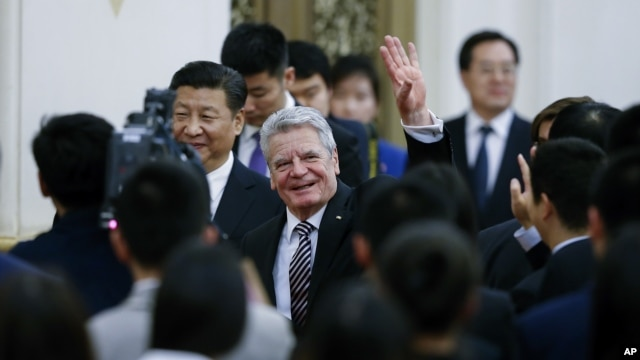 German President Joachim Gauck waves next to Chinese President Xi Jinping as they attend the opening ceremony of the Sino-German Youth Friendly Exchange Year at the Great Hall of the People in Beijing, March 21, 2016.