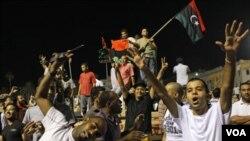 Rakyat Libya merayakan kemenangan setelah berhasil merebut dan menggeledah kediaman Gaddafi di Tripoli (24/8).