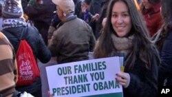 Un grupo de profesores de leyes aprueban la acción ejecutiva del presidente Barack Obama sobre inmigración, al igual que esta inmigrante que se la agradece con un letrero.