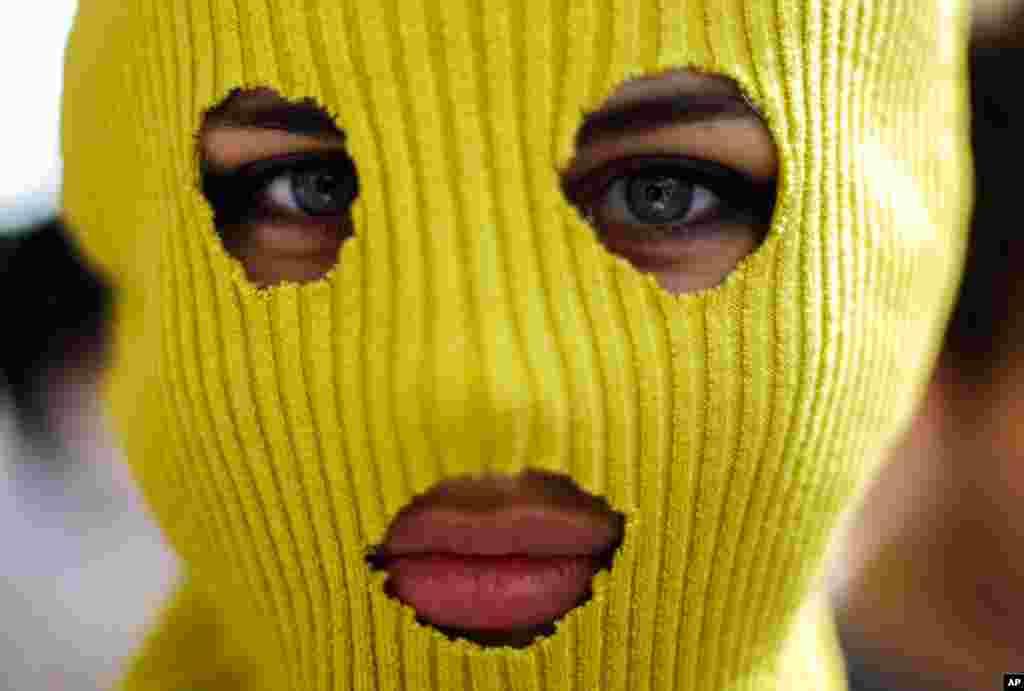 """俄罗斯驻柏林大使馆外面一名戴着面罩的示威人士参加支持""""Pussy Riot""""三名歌手的抗议活动"""