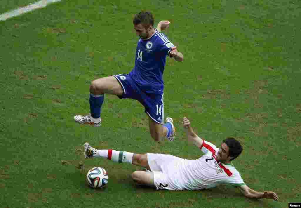 Bosniya komandasının oyunçusu Tino Sven Süsik və yerə yıxılan İran komandasının oyunçusu Xosrov Heydəri - 25 iyun, 2014