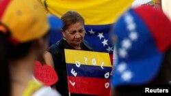 Una ciudadana venezolana residente en México sostiene un rótulo con el nombre de López.