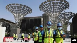 FILE - In this Oct. 8, 2019, file photo, technicians walk at the under construction site of the Expo 2020 in Dubai, United Arab Emirates. (AP Photo/Kamran Jebreili, File)