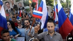 This photo from the Syrian news agency SANA shows Syrians in front of the Russian Embassy in Damascus expressing their thanks to Russia for its intervention, Oct. 13, 2015. Few Syrians who leave their country, however, are finding Russia to be a safe haven.
