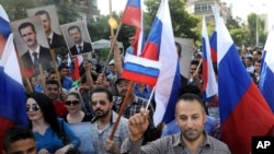 This photo from the Syrian official news agency SANA shows Syrians rallying in front of the Russian Embassy in Damascus to show their thanks to Russia for its intervention in Syria, Oct. 13, 2015. But few Syrians who leave their country are finding Russia welcoming.