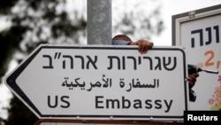 Seorang pekerja memasang papan tanda jalan yang menunjukkan arah ke Kedutaan Besar AS di Yerusalem (8/5).