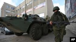 سربازی در لباس نظامی بدون نشان دولتی در برابر دادگاه نظامی اوکراین در سیمفروپل نگهبانی می دهد - شبه جزیره کریمه، بیستم مارس
