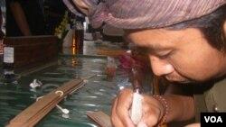 Proses penulisan aksara Bali pada lembaran lontar, sebagai upaya pelestarian bahasa dan sastra Bali dan Jawa kuno (VOA/Muliarta).