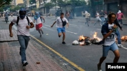 Opposition students run from Venezuelan police as they protest President Nicolas Maduro's government, Caracas, Feb. 12, 2015.