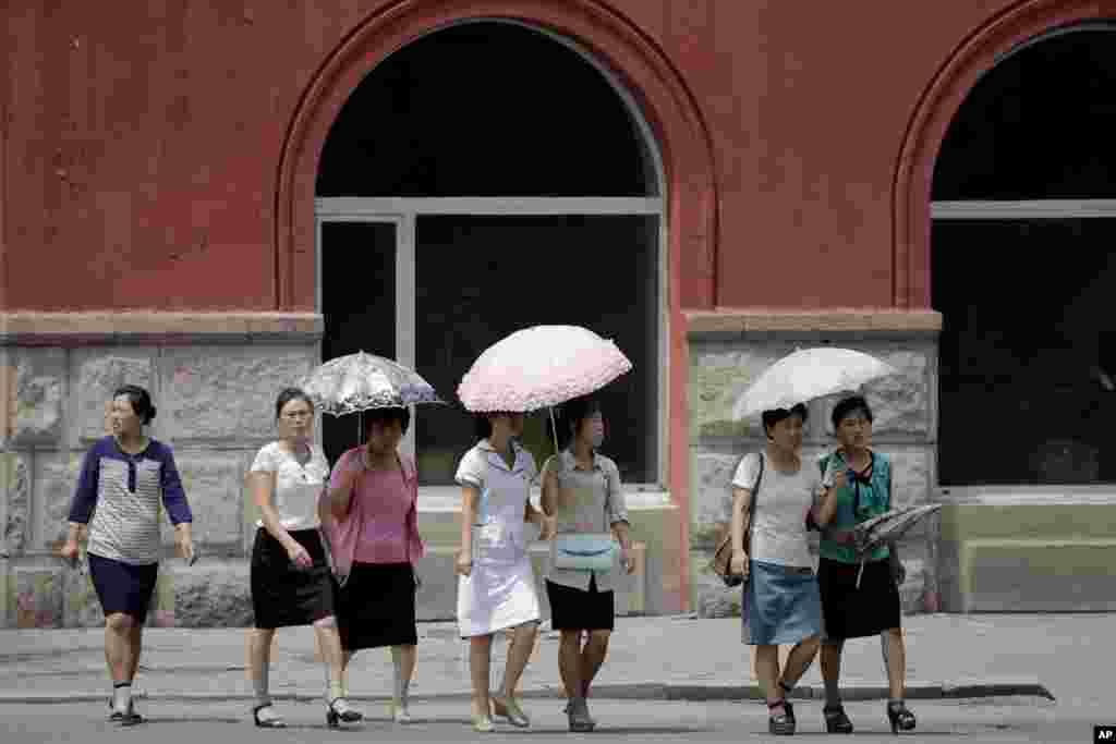 뜨거운 여름 햇살을 피하기 위해 양산을 나눠 쓴 평양 거리의 여성들.