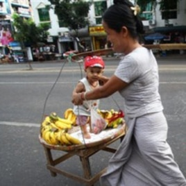 A street vendor carries her son and bananas on a street in Rangoon.