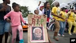 Anak-anak memegang poster Mandela bertuliskan Madiba, nama dimana ia biasa dipanggil di Afrika Selatan, berpawai bersama warga di dekat rumah Mandela di Soweto, Johannesburg 6/12/2013.