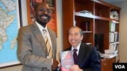 Rafael Marques à esquerda entregando o seu livro Diamantes de Sangue a Daniel Yamamoto do departamento de Estado americano