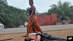 Một phụ nữ đi ngang một người nằm trên đường trong thủ đô Monrovia của Liberia, mà người ta nghi là bị nhiễm virut Ebola, 12/9/14