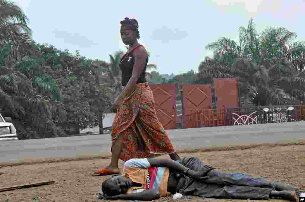A woman looks down as she walks past a man suspected of suffering from the Ebola virus in a busy part of Monrovia, Liberia, Sept. 12, 2014.