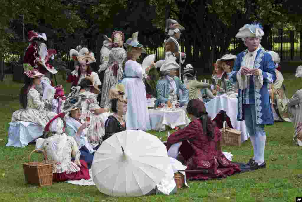 People dressed in costumes relax besides the Friedenstein Castle at the Baroque Festival in Gotha, Germany, Aug. 26, 2017.