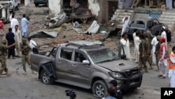 Giới chức an ninh Pakistan và nhân viên cứu hộ xem xét hiện trường vụ nổ bom ở ngoại ô Peshawar, ngày 30/6/2013.