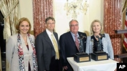 Secretary Clinton presents the World Food Program's 2011 George McGovern Leadership Award to Howard Buffett and Bill Gates, at the Department of State; also pictured is WFP Executive Director Josette Sheeran.