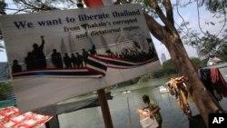 Seorang demonstran anti-pemerintah membawa kotak berisi barang-barang miliknya di Taman Lumpini, Bangkok (7/3).