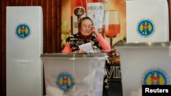 A woman casts a ballot during a parliamentary election at a polling station in Laloveni near Chisinau, Moldova, Nov. 30, 2014.