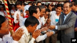 Cambodian Prime Minister Hun Sen, right, greets villagers as he arrives for an inauguration ceremony of a road funded by Japan for its official use at Kdey Takoy village, outside of Phnom Penh, Cambodia, Tuesday, March 13, 2018. (AP Photo/Heng Sinith)