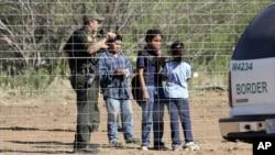 Imigran anak-anak bersama petugas patroli perbatasan di Laredo, Texas. (Foto: Dok)