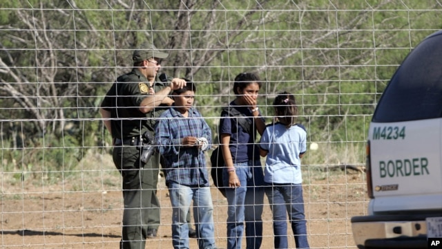 FILE - A Border Patrol agent stands on a ranch fence line with children taken into custody in South Texas brush country north of Laredo, Texas.