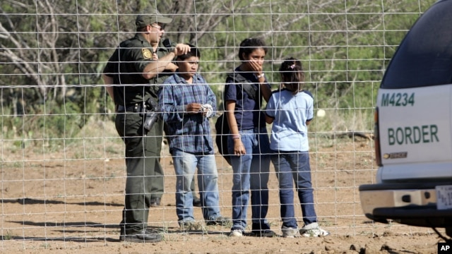FILE - A Border Patrol agent stands at a ranch fence line with children taken into custody in southern Texas brush country north of Laredo.
