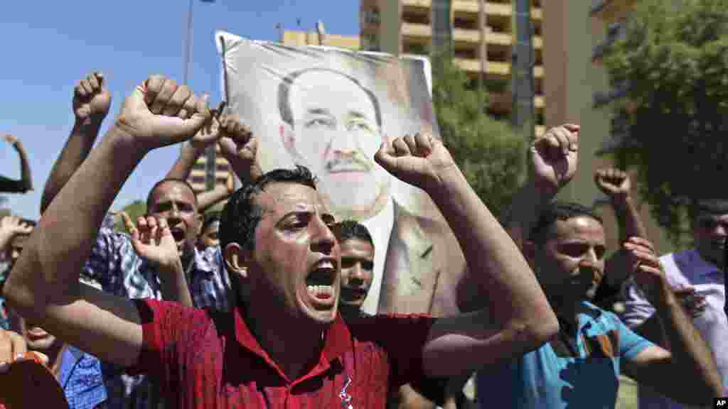 Iraqis chant pro-government slogans and display placards bearing a picture of embattled Prime Minister Nouri al-Maliki during a demonstration in Baghdad, Iraq, Aug. 11, 2014.