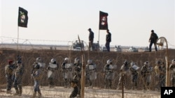 In this file photo provided by the People's Mujahedeen Organization of Iran, Iraqi police stand guard outside the opposition group's camp northeast of Baghdad, Iraq.