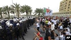 ພວກປະທ້ວງຕໍ່ຕ້ານລັດຖະບານ ພາກັນຮ້ອງຄໍາຂວັນຕ່າງໆ ຕໍ່ພວກຕໍາຫລວດປາບການຈະລາຈົນ ທີ່ນະຄອນຫລວງ Manama, Bahrain, ວັນທີ 13 ມີນາ, 2011
