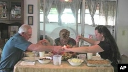 A family prays before Thanksgiving dinner.
