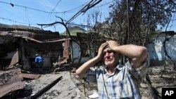 An ethnic Uzbek holds his head in his hands as he stands beside the wreckage of his burned out home in Osh (file photo – 14 June 2010)