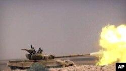 伊斯兰国激进分子的网站在2015年5月20日公布的这张照片显示,载有伊斯兰国组织激进分子的坦克在叙利亚霍姆斯和帕尔米拉之间的一条路上与叙利亚政府军交火