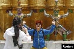 Du khách Trung Quốc chụp hình trong tư thế tương tự như bức tượng tại Grand Palace ở Bangkok, tháng 3/2015.