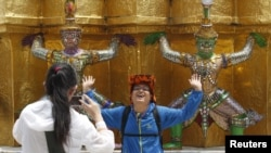 FILE - A Chinese tourist strikes a similar pose to statues as they visit the Grand Palace in Bangkok.