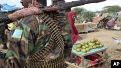 FILE - A fruit seller looks across as a Somali government soldier stands guard in Afgoye, west of the capital Mogadishu, in Somalia.