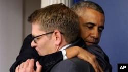 Obama abraza a Jay Carney en la Casa Blanca tras anunciar la partida de su portavoz.