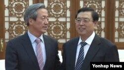 장더장 중국 전국인민대표대회 상무위원장(오른쪽)이 지난 20일 베이징 인민대회당에서 정몽준 한국 새누리당 의원을 만나 악수하고 있다.
