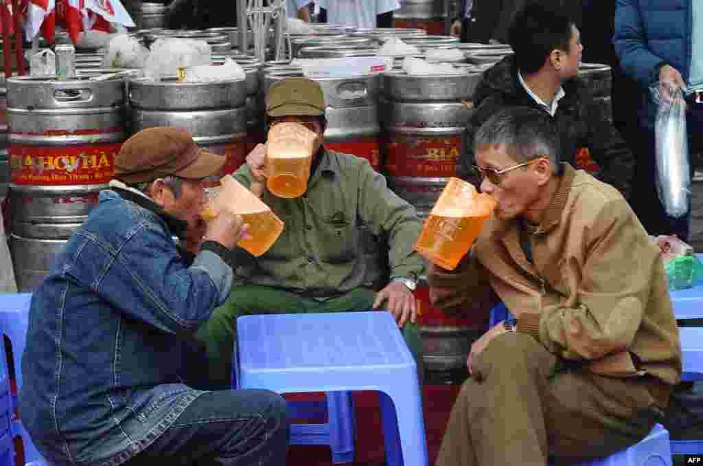 Men drink beer during a local annual beer festival in Hanoi, Vietnam.