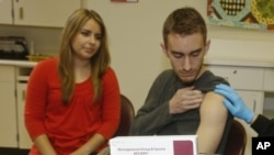 FILE - Meningococcal meningitis survivor and vaccination advocate Leslie Meigs looks on as her brother Andrew (18), a college student in Texas, receives Bexsero(R), a meningococcal group B vaccine approved by the FDA for ages 10-25.