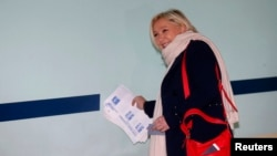 French National Front political party leader and candidate Marine Le Pen collects ballots as she arrives at a polling station during the first round of the regional elections in Henin-Beaumont, France, Dec. 6, 2015.